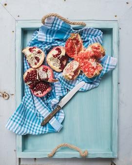 Rode en witte granaatappels met mes in blauw dienblad over lichte geschilderde houten achtergrond