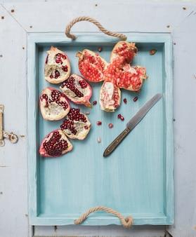 Rode en witte granaatappels met mes in blauw dienblad