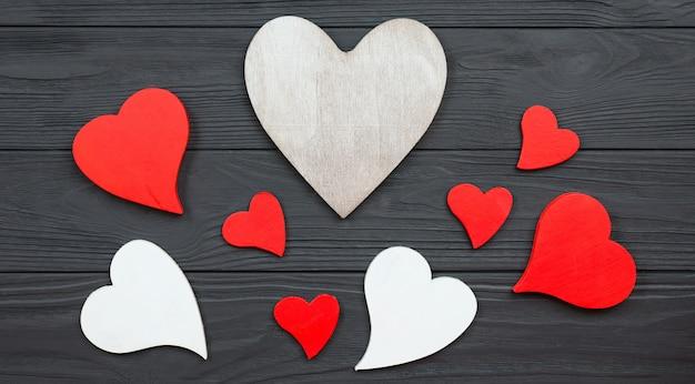 Rode en witte harten op donkere houten oppervlak