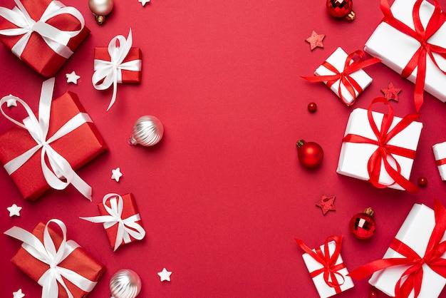Rode en witte kerst geschenkdozen op rode achtergrond bovenaanzicht