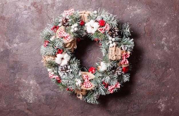 Rode en witte kerstkrans met strikken en katoenen bloemen