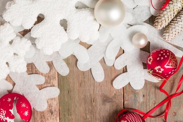 Rode en witte kerstmisbal en linten op houten achtergrond dichtbij sneeuwvlok en pijnboom