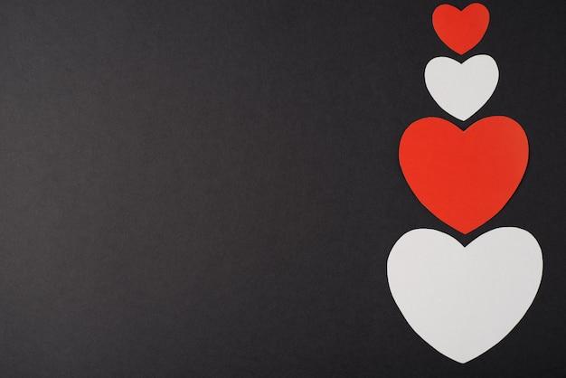 Rode en witte papieren harten op de donkere achtergrond. plat lag, bovenaanzicht. valentijnsdag concept.