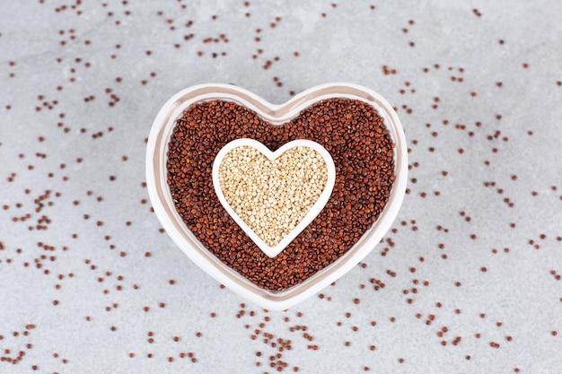 Rode en witte quinoa in hartvormige kom op stenen ondergrond