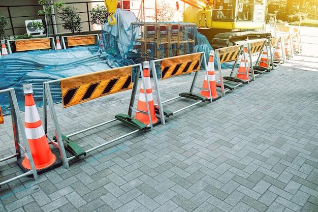 Rode en witte verkeerskegels die bouwmachines op de bouwplaats in stad blokkeren
