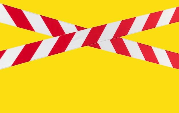 Rode en witte waarschuwingslijnen van barrièretape verbieden doorgang. afzetband op geel isolaat. barrière die het verkeer verbiedt. waarschuwing onveilig gebied niet betreden. concept van geen toegang. ruimte kopiëren