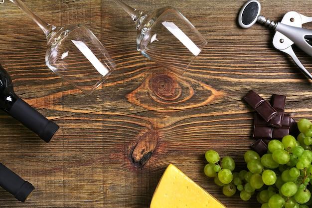Rode en witte wijnflessen, druiven, kaas en glazen over houten tafel. bovenaanzicht met kopie ruimte. stilleven. plat leggen