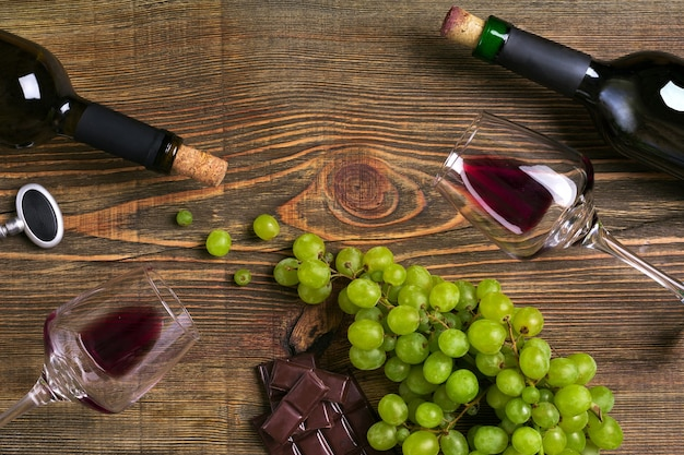 Rode en witte wijnflessen druivenchocolade en glazen over houten tafelblad met kopieerruimte