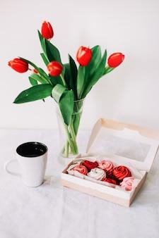 Rode en witte zoete zephyrs met rode tulpen en kopje koffie