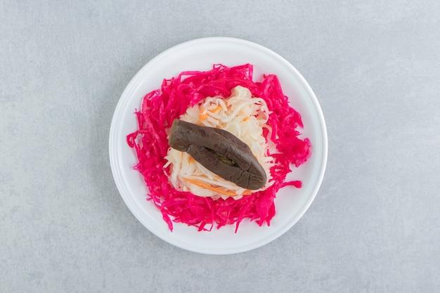 Rode en witte zuurkool met aubergine op witte plaat.