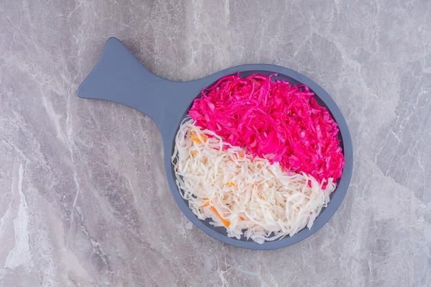 Rode en witte zuurkool op een houten pan, op het marmer.