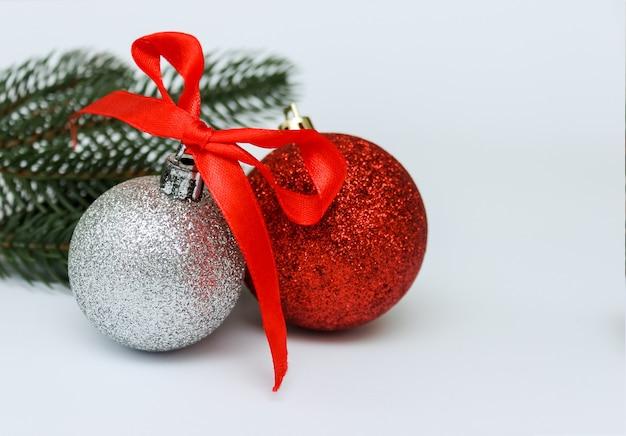 Rode en zilveren kerstbal met rood lint.