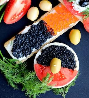 Rode en zwarte knapperige crackersandwiches met groenten. bovenaanzicht