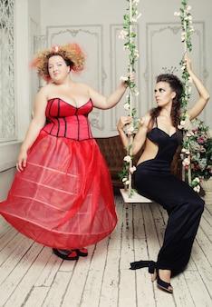 Rode en zwarte koninginnen poseren met schommel