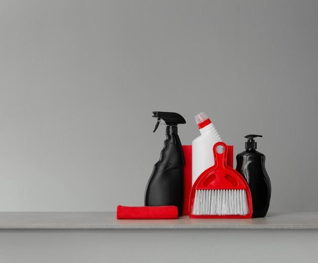 Rode en zwarte reinigingsset - schep en bezem, doeken, toiletwasmiddel, afwasmiddel en spray