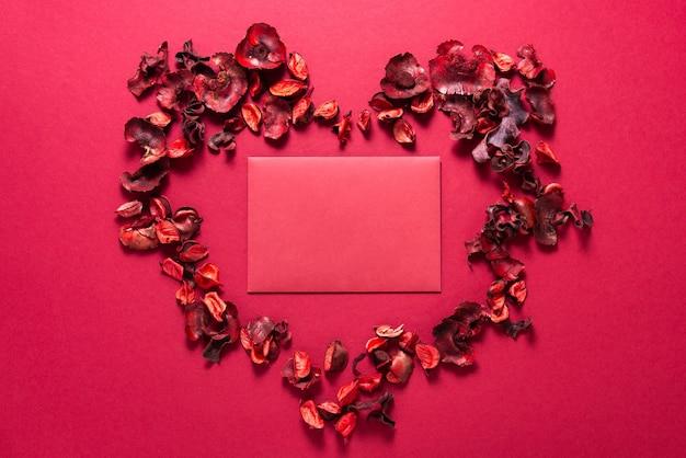Rode envelop en droge bloemen, valentijnsdag aanwezig
