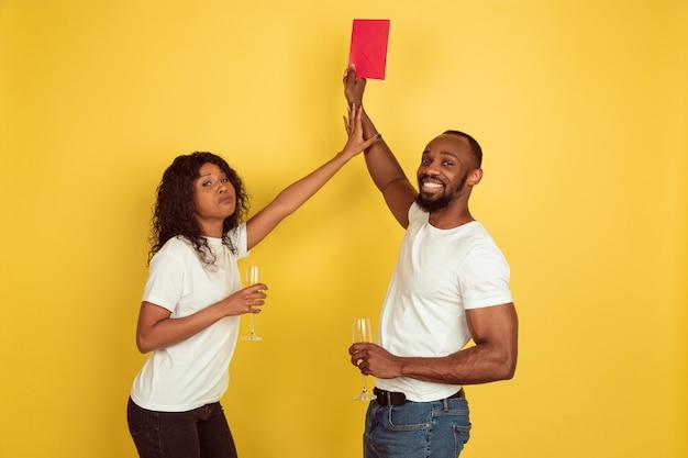 Rode envelop geven. gelukkig afrikaans-amerikaans paar geïsoleerd op gele muur. concept van menselijke emoties, gezichtsuitdrukking, liefde, relaties, romantische vakanties.