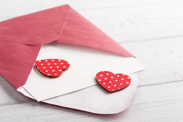 Rode envelop met leeg papier en rode harten