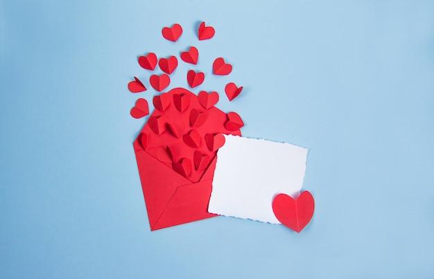 Rode envelop met rode harten op blauwe achtergrond, kaart voor tekst en kopieer de ruimte