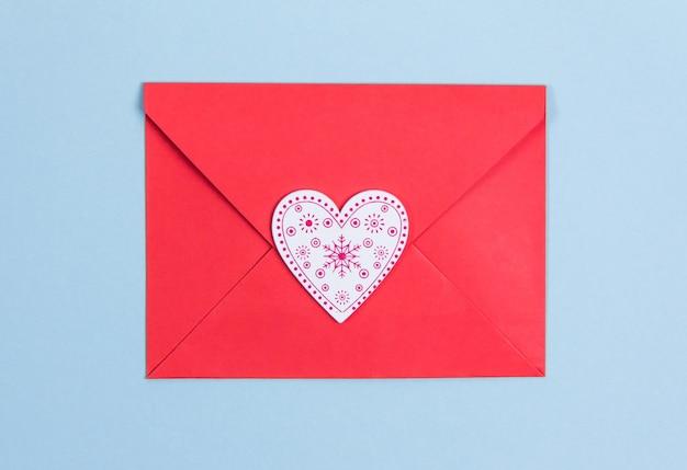 Rode envelop met rode harten op blauwe achtergrond, kopieer ruimte valentijnsdag