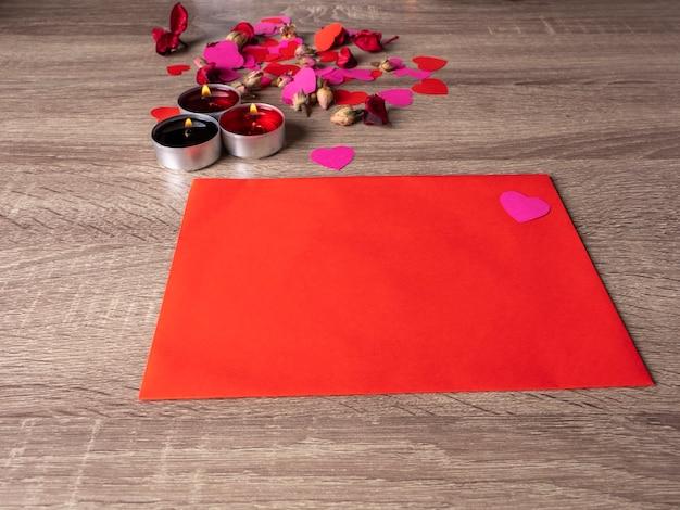 Rode envelop naast kaarsen met rode rozenblaadjes en harten op tafel