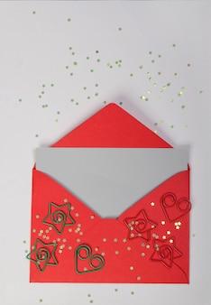 Rode envelop versierd met sterren en harten, op een witte achtergrond. nieuwjaar decoratie.