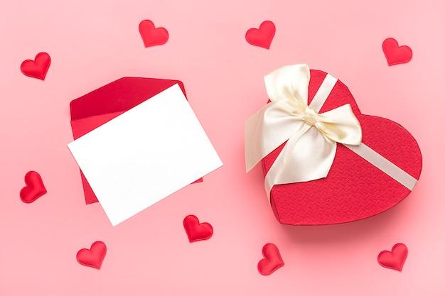 Rode envelop, wit schrijfpapier, harten, geschenkdoos met lint strik op roze achtergrond happy valentine's day concept
