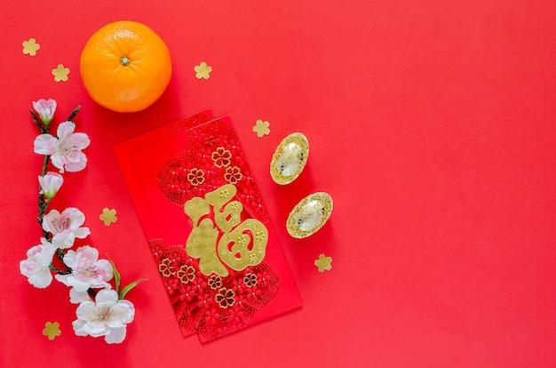 Rode enveloppakketten of ang bao (woord betekent rijkdom) met goudstaven, oranje en chinese bloesembloemen voor chinees nieuwjaar op rode achtergrond.