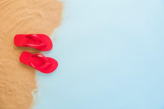 Rode flip flops op zand