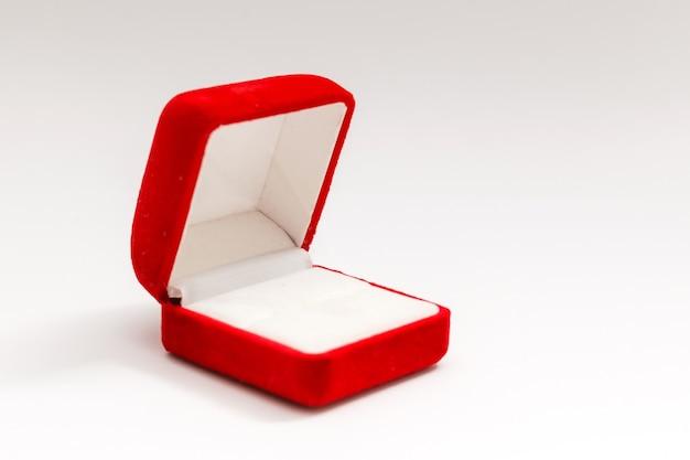 Rode fluwelen doos voor de ring, geopend, geïsoleerd over de witte achtergrond