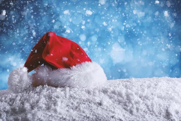 Rode fluwelen kerstmuts van de kerstman in de sneeuw