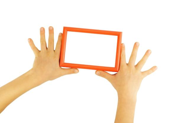 Rode fotolijst tussen de handen van kinderen geïsoleerd op een witte muur.