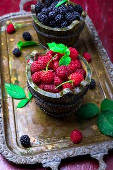 Rode frambozen en bramen met blad in een mand op vintage metalen dienblad.