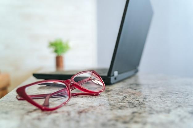 Rode frame glazen op tafel en laptop op de achtergrond