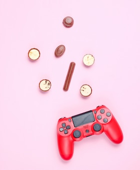 Rode gamepad en chocolade snoep op roze pastel achtergrond