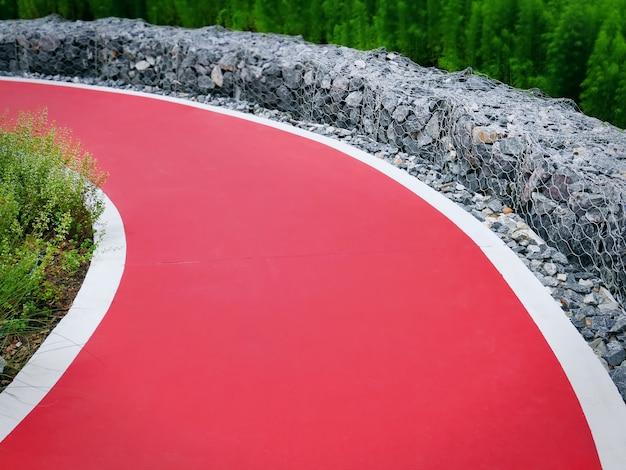 Rode gebogen enkele rijstrook weg met rotsen als hek
