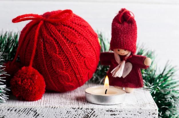 Rode gebreide kerstbal en decoratie met brandende kaars in wit scandinavisch interieur. kopieer ruimte voor greting