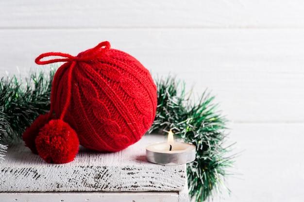 Rode gebreide kerstbal en decoratie met brandende kaars in wit scandinavisch interieur