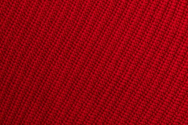Rode gebreide wollen stoffenachtergrond of textuur