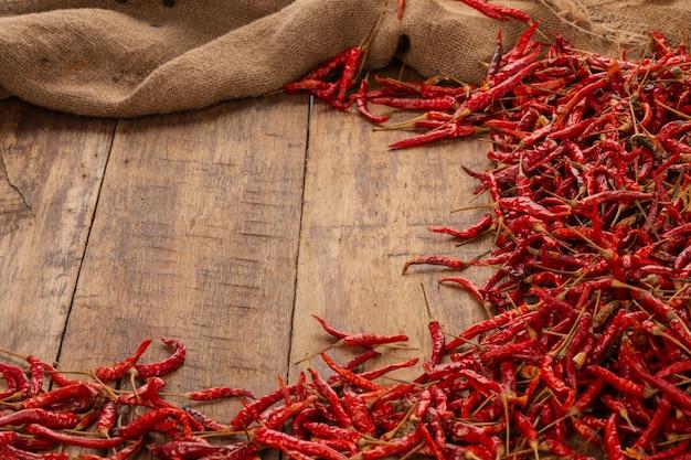 Rode gedroogde pepers die op de plank worden gestapeld.