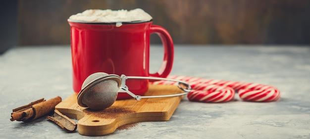 Rode geëmailleerde kerstbeker met warme chocolademelk en slagroom, kaneelstokjes, anijssterren en hartige zandkoekjes, suikerkoekjes en zuurstokken op licht