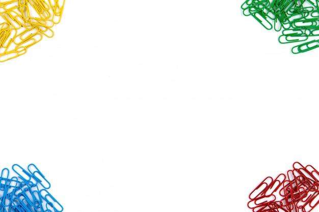 Rode, gele, blauwe en groene briefpapierclips liggen in verschillende hoeken van het vel op een witte achtergrond. bovenaanzicht en kopieer ruimte.