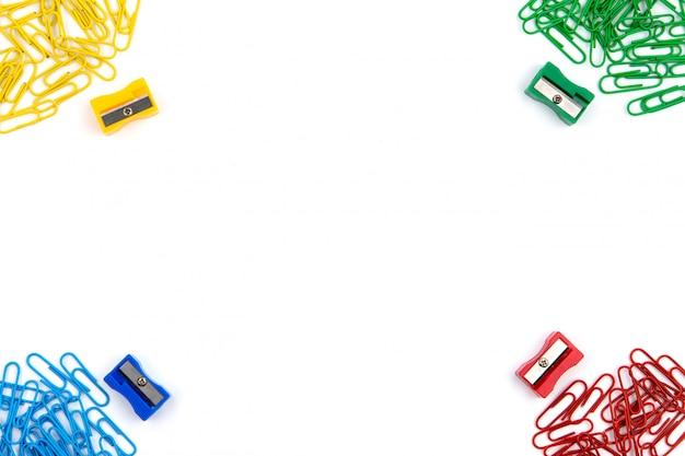 Rode, gele, blauwe en groene briefpapierklemmen en puntenslijpers liggen in verschillende hoeken van het vel