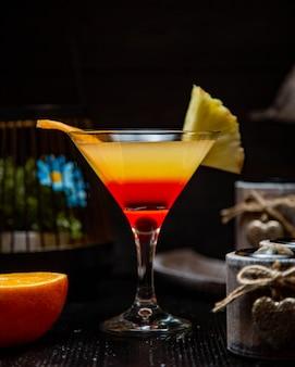 Rode gele cocktail met ananasfruit en sinaasappel.