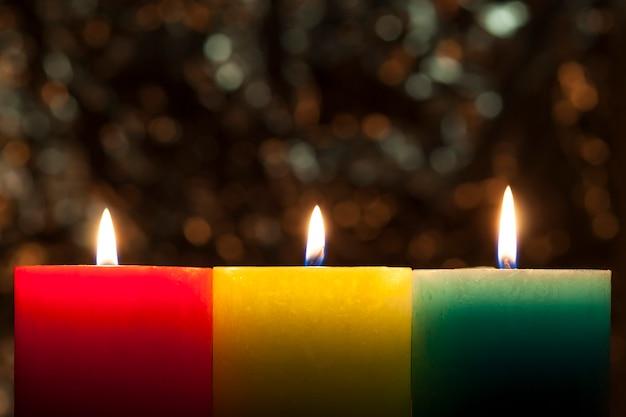 Rode, gele en groene kleurrijke kaarsen met vage bokeh achtergrond. kerstmis en nieuwjaar kopie ruimte.