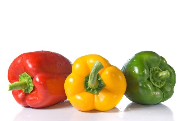 Rode, gele en groene peper met waterdalingen die op wit worden geïsoleerd