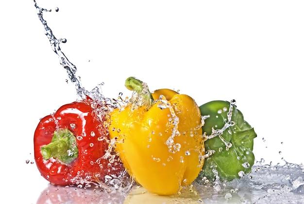 Rode, gele en groene peper met waterplons die op wit wordt geïsoleerd