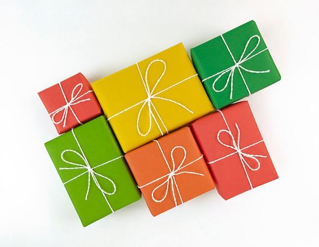 Rode, gele, groene en oranje geschenkdozen op een witte achtergrond.