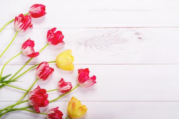Rode, gele tulpenbloemen op houten achtergrond.