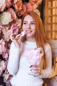 Rode geleide glimlachende jonge vrouw die het katoenen roze suikergoed eten die zich tegen bloemdecoratie bevinden
